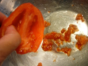 5. Cut tomatoes in half.  Scoop out the seeds trim the stem end.  Your tomatoes are now ready to use!