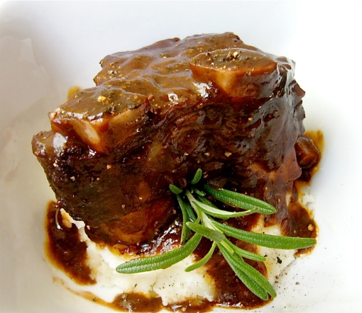 Braised short ribs with mashed potatoes and a rosemary sprig garnish